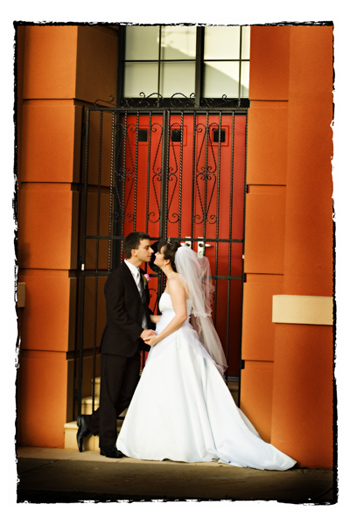 The couple in front of a rich red door with Iron Grill